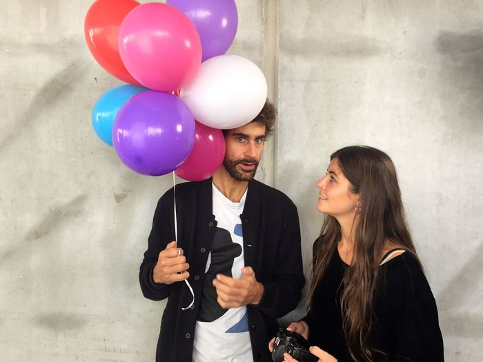 Young couple holding balloons