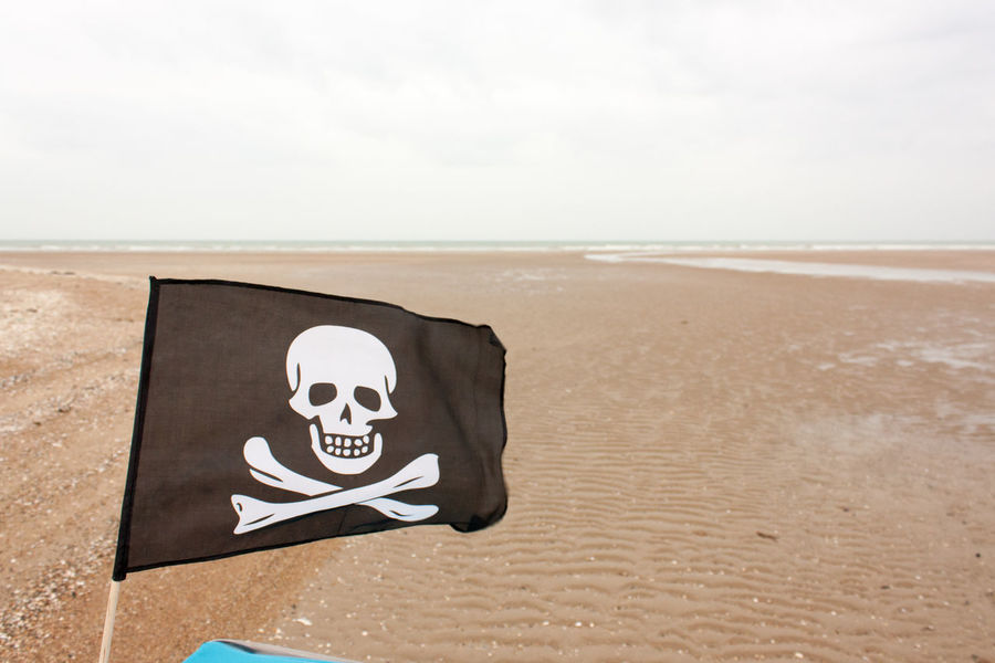 Pirate Pirate Flag Beach Day Horizon Horizon Over Water Jolly Roger Nature No People Outdoors Sand Scenics Sea Sky Water Windy