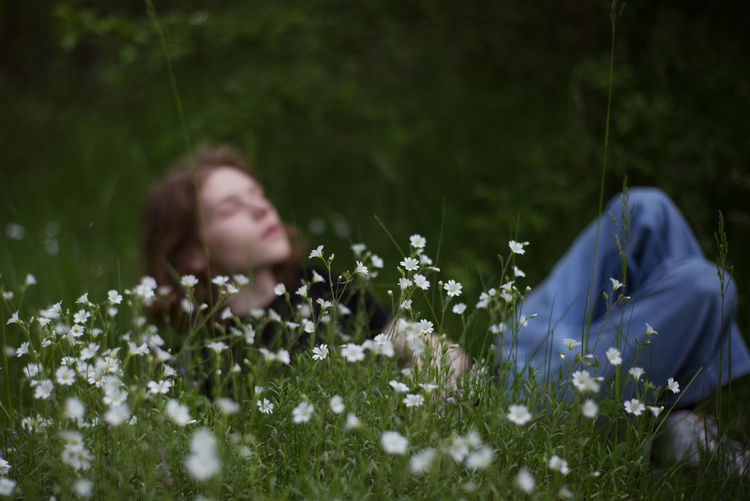 Rear view of woman amidst flowering plants on field
