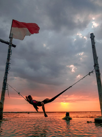 Man resting on hammock over sea against cloudy sky during sunset