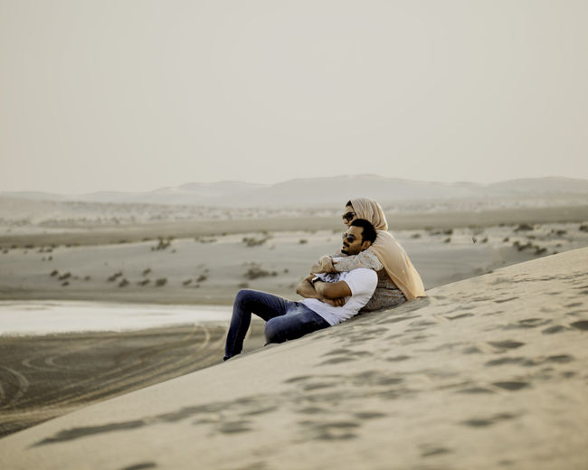 Couple sitting on sand in desert