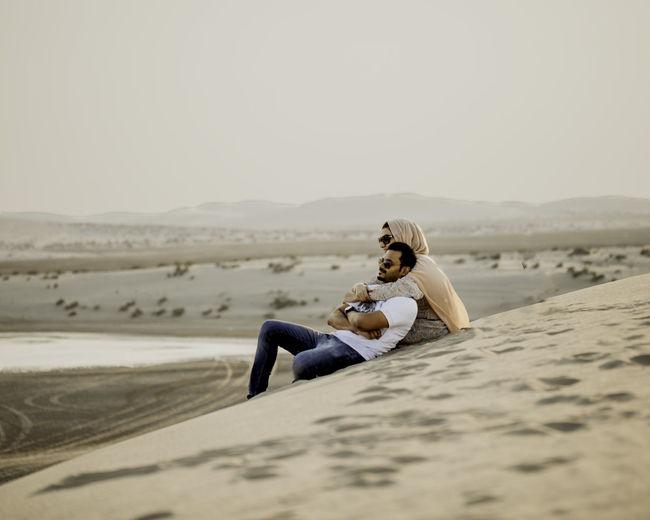 Couple sitting on sand in desert