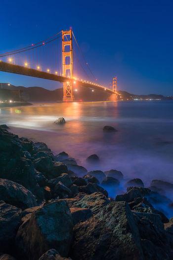 Illuminated suspension bridge over sea at night