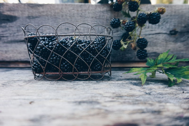 Close-up of blackberries in metal container on wooden table