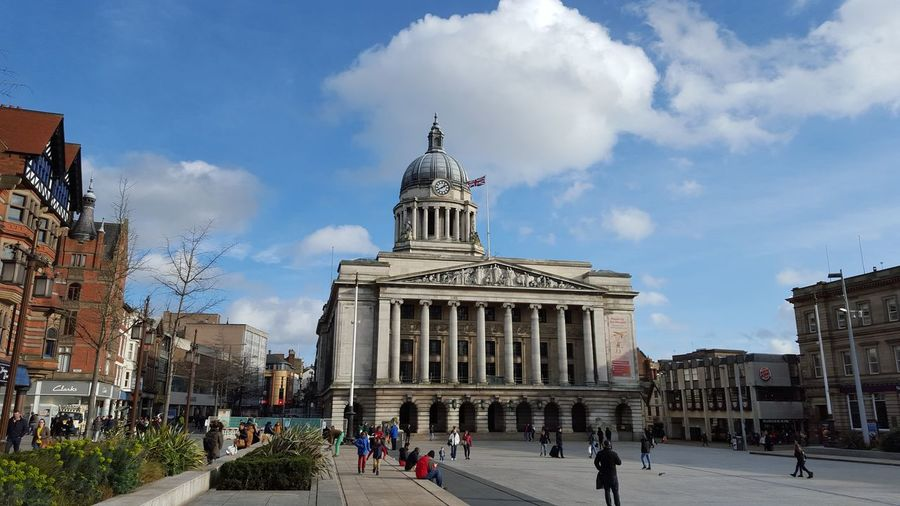 People at nottingham council house against cloudy sky