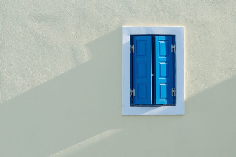 Blue window on white wall of building