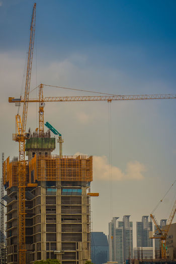 Crane at construction site against sky in city