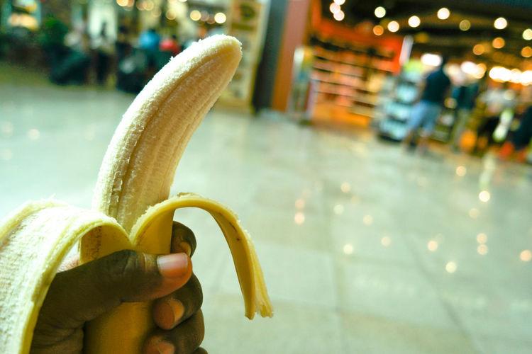Close-Up Of Hand Holding Banana