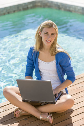 Young woman using laptop while sitting at poolside