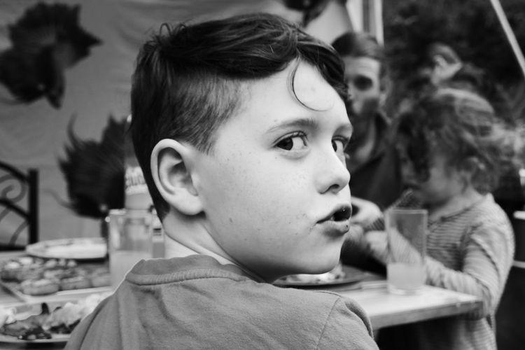 Rear view portrait of boy having food on table