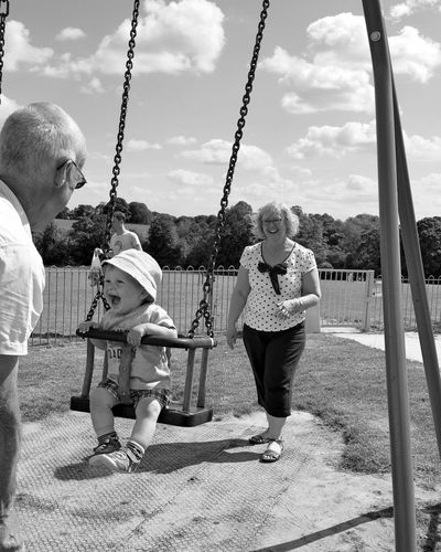 Casual Clothing Child Childhood Enjoyment Full Length Fun Fun Girls Grandchild Grandparents Hanging Happiness Happy Holding Leisure Activity Lifestyles One Person Park Playground Rope Sitting Smile Swing Swinging Togetherness