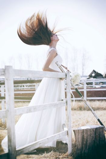 Beautiful Bride With Tousled Hair Standing By Railing In Pen Against Clear Sky