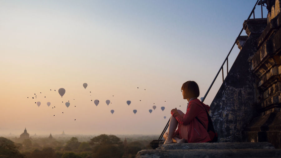 Woman Sitting On Stairway While Looking At Hot Air Balloons Against Sky During Sunset