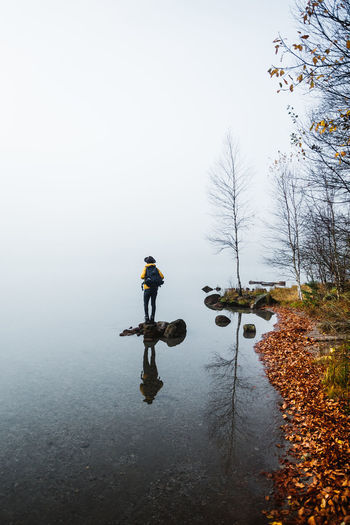 Real People Full Length One Person Nature Water Sky Lifestyles Day Men Fog Leisure Activity Tree Plant Rear View Transportation Beauty In Nature Outdoors Warm Clothing Riding Change Hiker Backpack Fog Over Water Reflection Hat A New Perspective On Life
