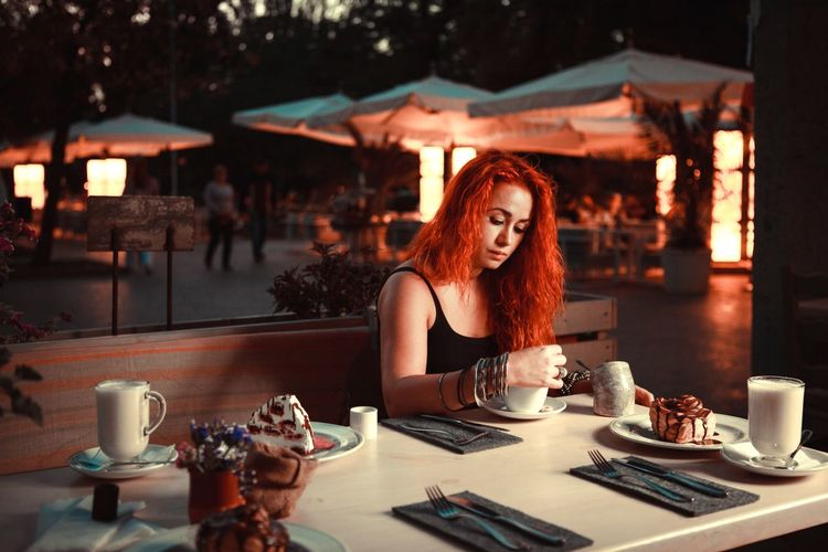 redhead girl having supper in a cafe at night in summertime Adults Only Adult Curly Hair Vibrant Colors Red Hair Redhead Redhair Nightphotography Night Lights Nightlife Night Photography Night View Nightshot Eating Cafe Time Cafe Lonely Alone Beautiful Woman Young Women Sitting Portrait Beauty Women Curly Hair Redhead Tea - Hot Drink Hot Drink Black Tea Non-alcoholic Beverage