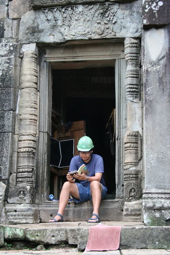 Cambodia Angkor Wat Angkorwat Cambodia Helmet Reading A Book Travel Travel Destinations Travel Photography UNESCO World Heritage Site Unusual Setting TakeoverContrast Dramatic Angles