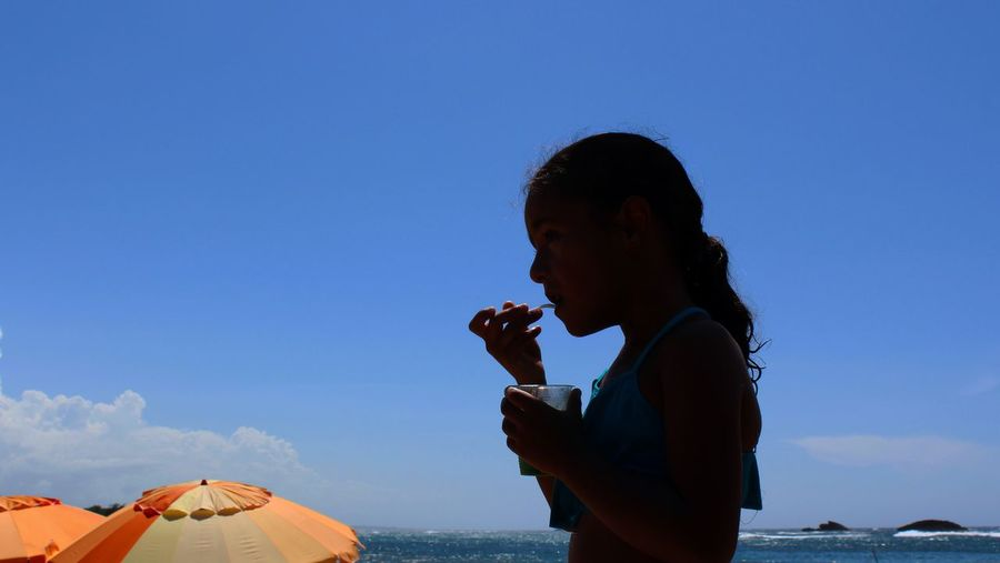 Side View Of Girl Eating Food Against Blue Sky On Sunny Day