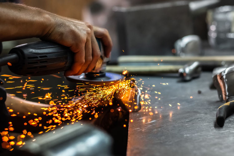 Cropped image of worker using grinder on metal in factory