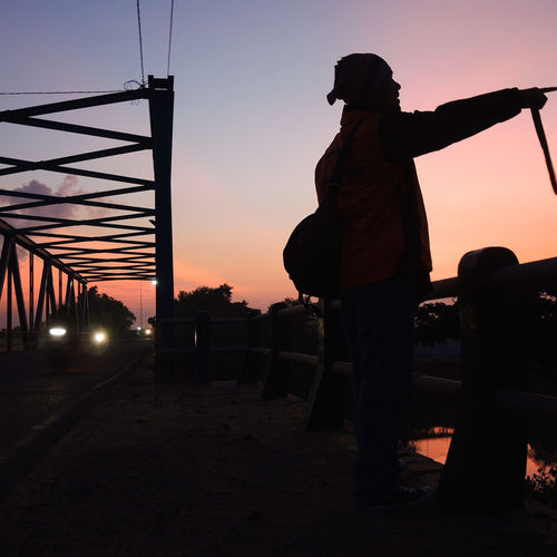 Man Standing By Bridge Against Sky During Sunset