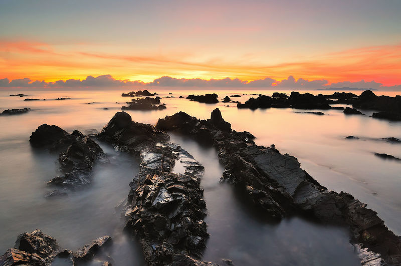 Beautiful sunrise or sunset over beach with great motion wave in Terengganu, Malaysia. Nature Background Beach Beauty In Nature Cloud - Sky Landscape Malaysia Nature No People Oceon Rock Rock - Object Scenics - Nature Sea Seascape Sky Skyscraper Solid Sunrise Sunset Tranquil Scene Tranquility Travel Destinations Water Waterfront