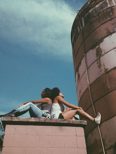 Low angle view of female friends sitting on built structure against blue sky