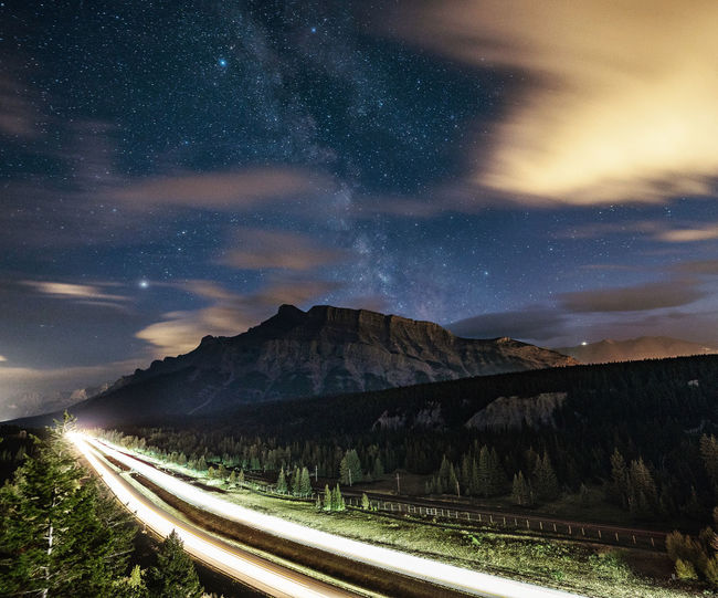 Road by mountains against sky at night