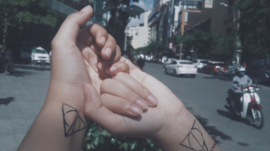 Cropped image of couple holding hands with tattoo