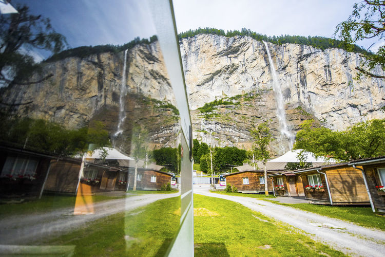 Architecture Beauty In Nature Building Exterior Built Structure Caravan Day Glass - Material Grass Land Mode Of Transportation Mountain Mountain Range Nature No People Outdoors Plant Scenics - Nature Sky Transportation Tree Window