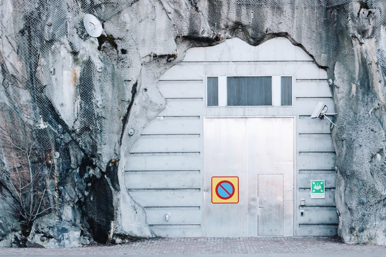No parking sign on door amidst rocky archway