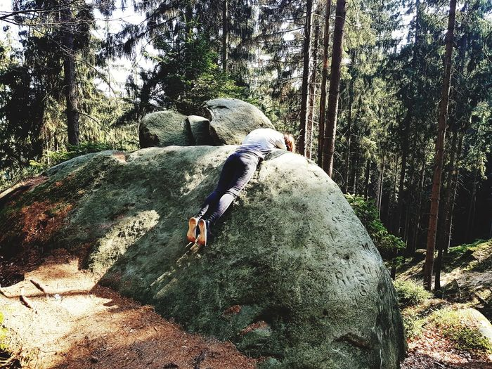 Man relaxing on rock in forest