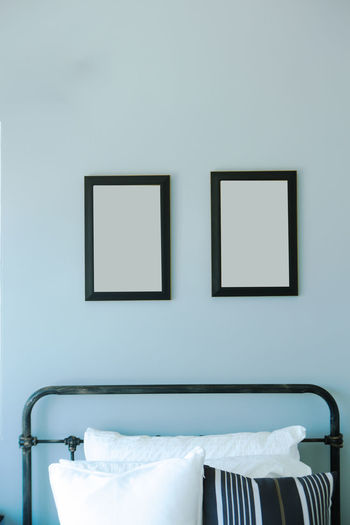 Cushions on bed against empty picture frames at home