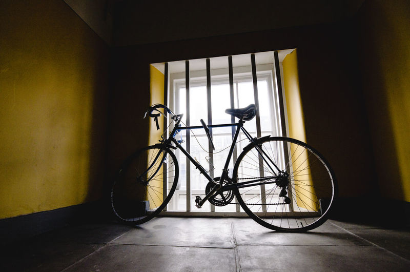 Bicycle parked by window in room