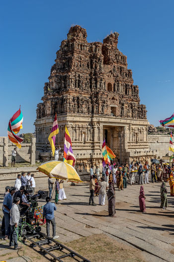 Camera Operator With Crew Filming Crowds Outside Temple At Hampi
