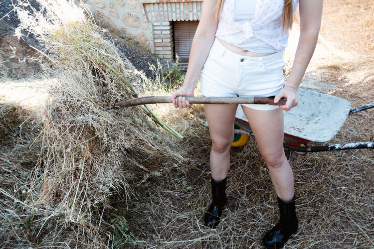 Blonde country girl with braids in her hair and straw hat cleaning grass in the field. rural scene.