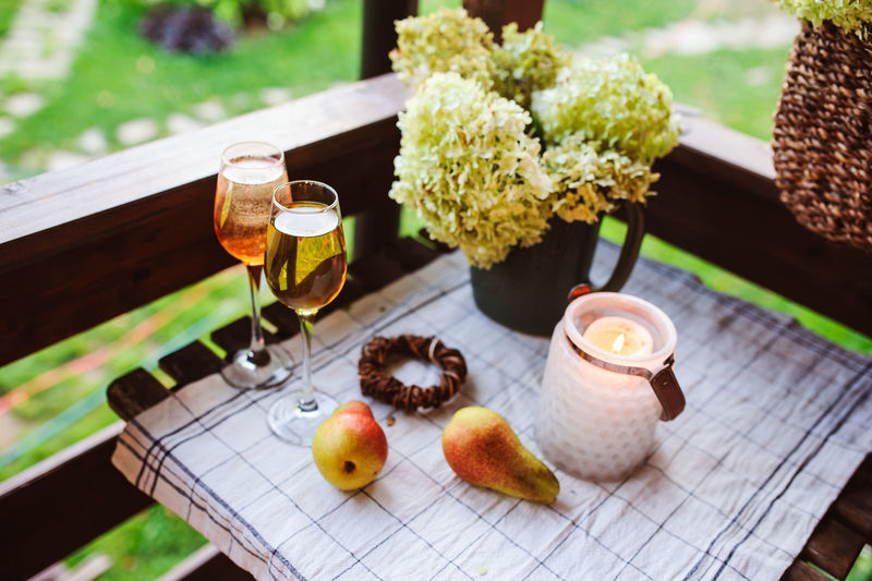 beautiful summer evening on wooden terrace or patio. Table with two glasses of wine, fruits and flowers Table Food And Drink Freshness No People Garden Summer Summertime Terrace Patio Calm Evening Wine Flowers Hydrangea Candle Relaxing Two Enjoying Life Lifestyles Country Life Country House