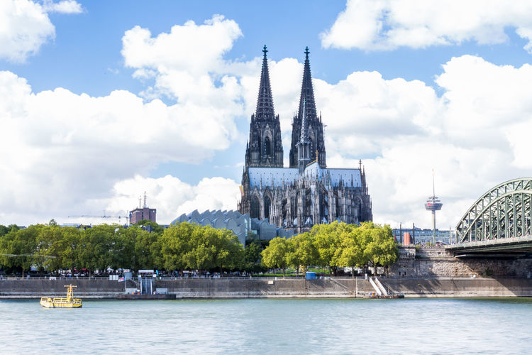 Scenic view of rhine river by cologne cathedral in city against sky
