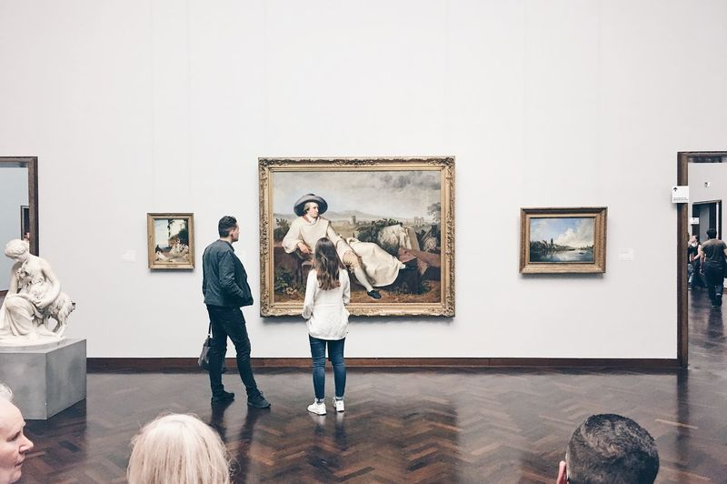 Rear view of man and woman standing in museum