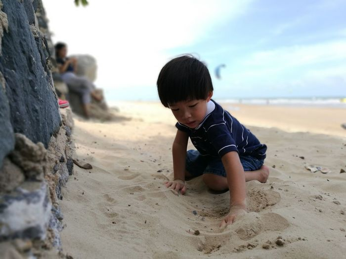 Cute boy playing with sand at beach