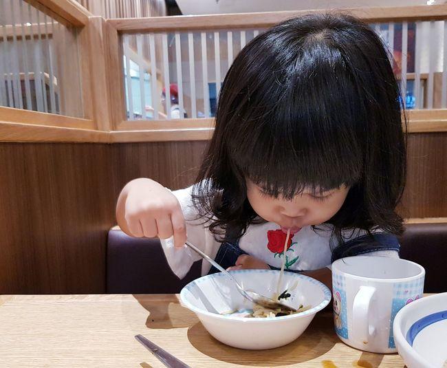 Girl having food at table in restaurant