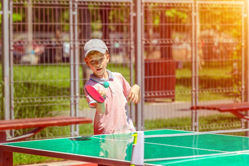 Boy playing table tennis during sunny day