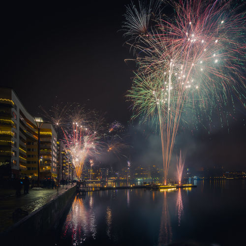 Firework display in city by river at night
