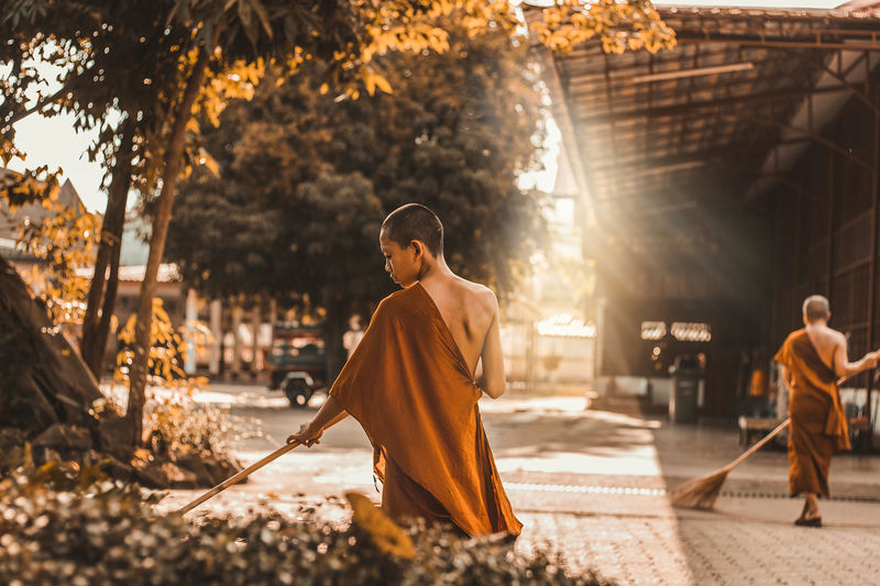 Rear view of teenage monk sweeping by plants on footpath