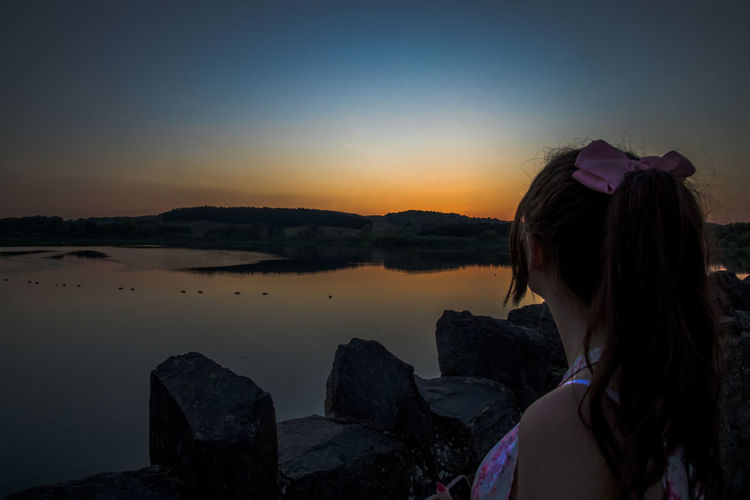Side view of woman looking at sea against sky during sunset