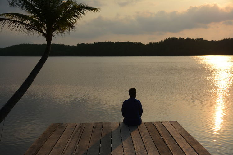 Rear view of man sitting on pier at sunset