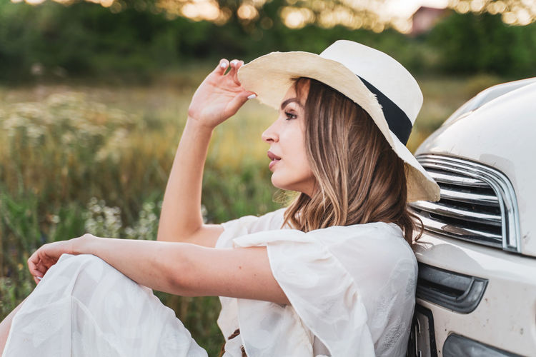 Side view of young woman in hat