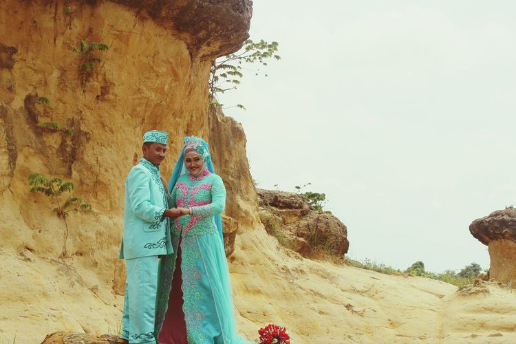Wedding couple standing against rock formation