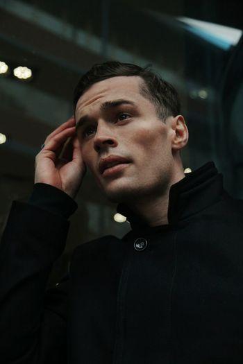 Handsome man wearing black shirt standing in building