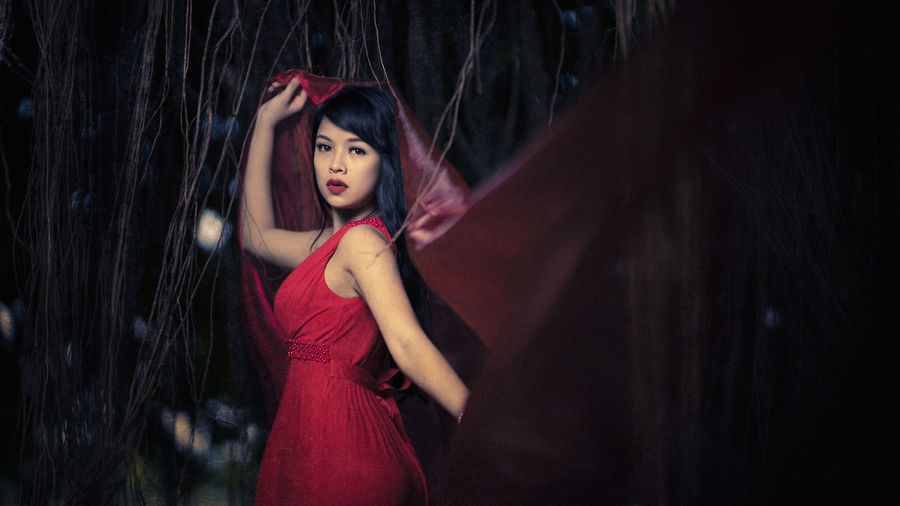 Portrait Of Young Woman Wearing Red Dress While Standing In Forest