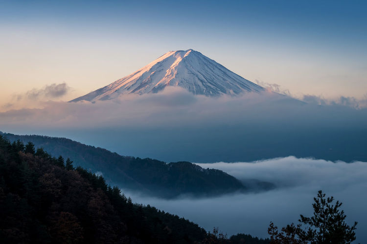 Mount Fuji enshrouded in clouds with clear sky from lake kawaguchi, Yamanashi, Japan Autumn Cloudscape Morning Trekking Beauty In Nature Blue Clouds And Sky Day Fog Forest Landmark Mist Mountain Nature No People Outdoors Scenics Sky Snowcapped Mountain Sunrise Tranquility Travel Destinations Tree