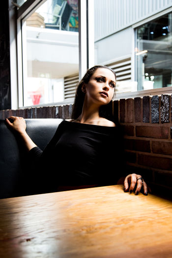 Thoughtful Young Woman Sitting At Cafe